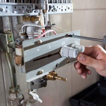Close-up of a gas water heater reparation
